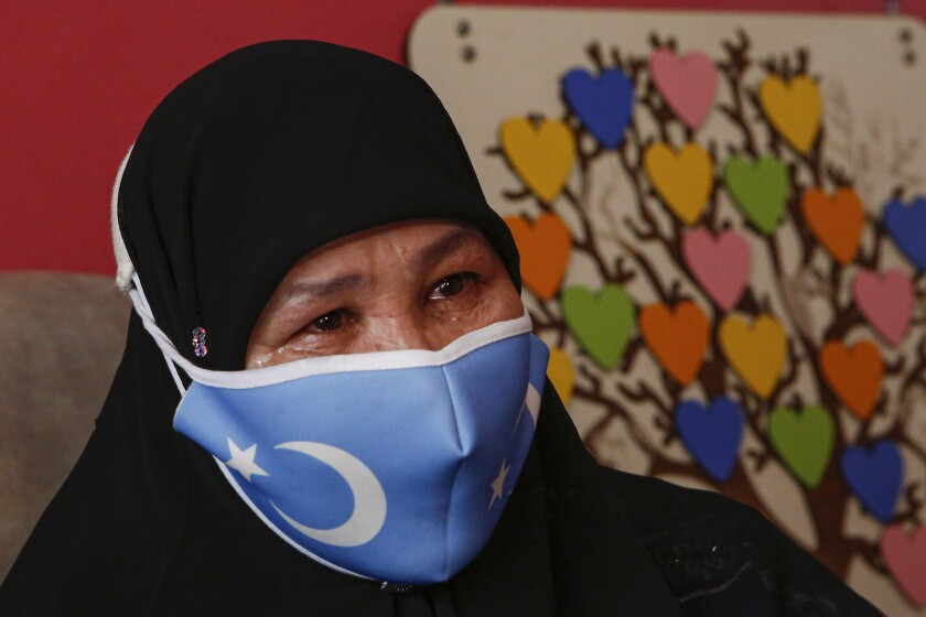 """Bumeryem Rozi, 55, an ethnic Uyghur who fled from China to Turkey, cries as she talks to The Associated Press, at her home, in Istanbul, Tuesday, June 1, 2021. Rozi, a mother of four, is one of three Uyghurs who described forced abortions and torture by Chinese authorities in China's far western Xinjiang region, ahead of giving testimony to a people's tribunal in London, which is investigating if Beijing's actions against the Uyghur ethnic group amount to genocide. Rozi, said authorities in Xinjiang rounded her up along with other pregnant women to abort her fifth child in 2007. """"I was 6.5 months pregnant. (AP Photo/Mehmet Guzel)"""