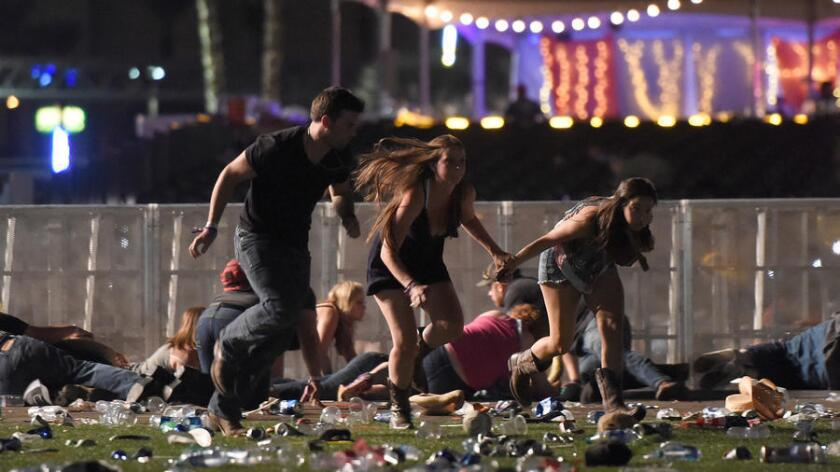 People run from the Route 91 Harvest country music festival after hearing gunfire Sunday night in Las Vegas. More than 50 people have died and another 500 are injured.