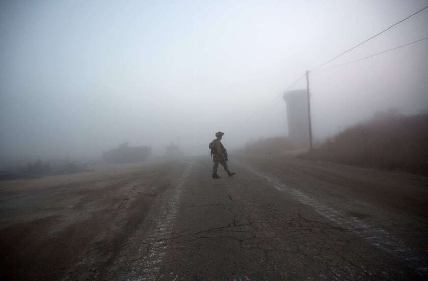 An Israeli soldier walks near the Quneitra border crossing in the Israeli occupied Golan Heights on Aug. 31.