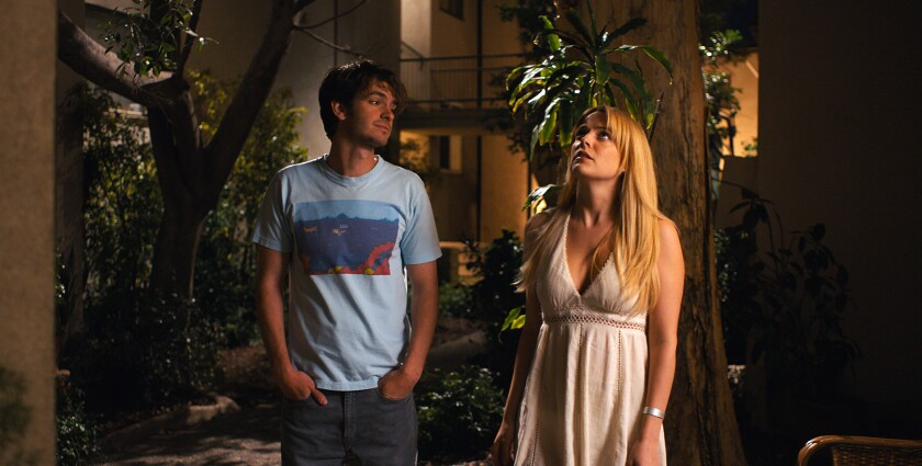 "This image released by A24 shows Andrew Garfield, left, and Riley Keough in a scene from ""Under the"
