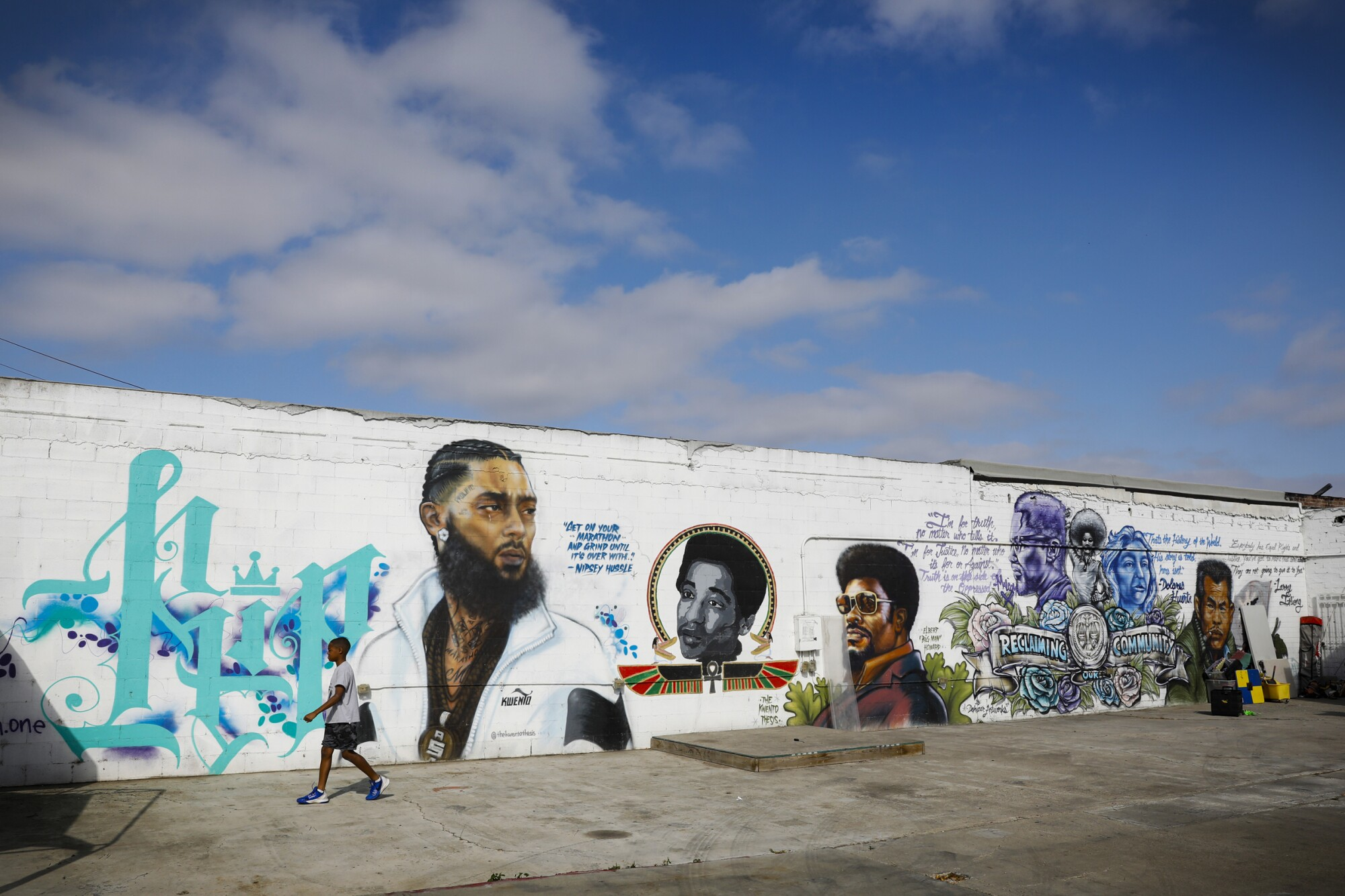"""A young boy walks by """"mural alley"""" near 63rd and Imperial Avenue in the Encanto neighborhood."""