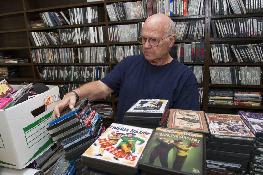 Guy Hanford sorts his wares, preparing for Saturday's reopening of Kensington Video.