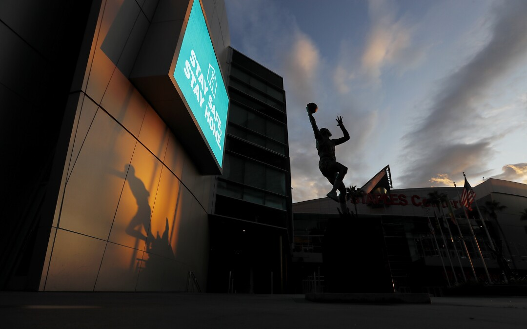 The shadow of a statue of Magic Johnson, left, and a statue of Kareem Abdul Jabbar are frozen in time at Staples Center, where the lights are off and events have been suspended due to the coronavirus pandemic.