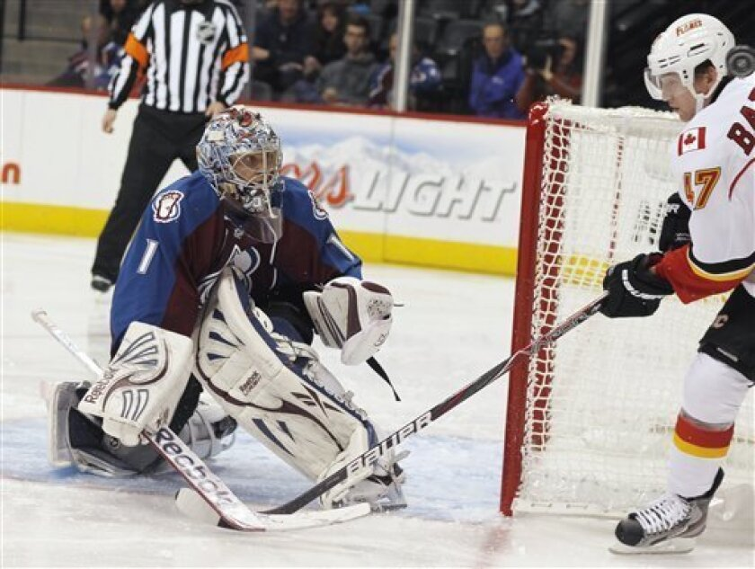 Calgary Flames left wing Sven Baertschi, right, of Switzerland, avoids the puck as it flies past his head after his wraparound shot was deflected by Colorado Avalanche goalie Semyon Varlamov, of Russia, during the second period of an NHL hockey game in Denver on Thursday, Feb. 28, 2013. (AP Photo/D