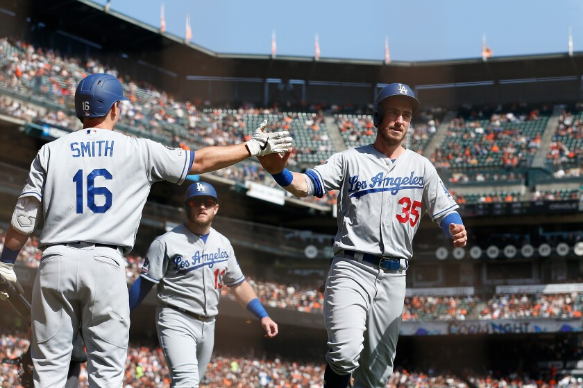 Cody Bellinger (35) and Max Muncy (13) celebrate with Will Smith (16) in a game against the Giants on Sept. 29 at Oracle Park.