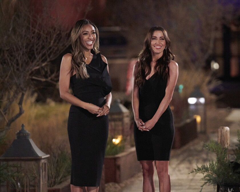 Two women in black dresses standing at a resort in the desert