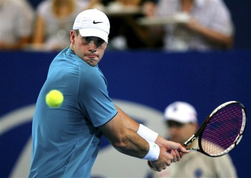 FILE - In a Jan. 5, 2010 file photo, John Isner of the United States plays against Australia's Lleyton Hewitt during their men's singles match at the Hopman Cup tennis tournament in Perth, Australia. Isner defeated Nicolas Mahut 6-3, 7-6 (5) Monday, Jan. 3, 2011 at the Hopman Cup in the first rematch since their 11-hour epic at Wimbledon. (AP Photo/Ross Swanborough, File)