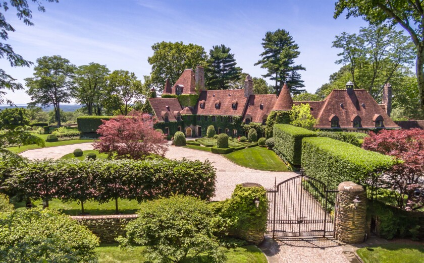 The estate features a 13,000-square-foot mansion surrounded by rolling lawns, hedges, water features and a tennis court.