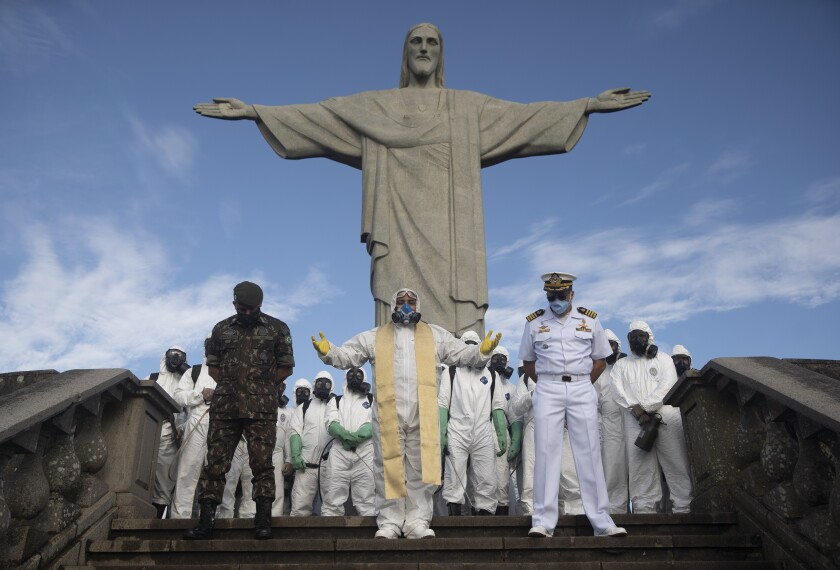 Catholic Priest Omar, center, leads a prayer as soldiers pause from disinfecting the Christ the Redeemer area, currently closed during the new coronavirus pandemic in Rio de Janeiro, Brazil, Thursday, Aug. 13, 2020. (AP Photo/Silvia Izquierdo)