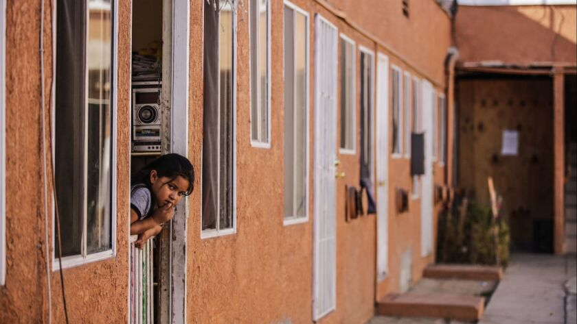 A child looks out on a courtyard in her South Los Angeles apartment complex.