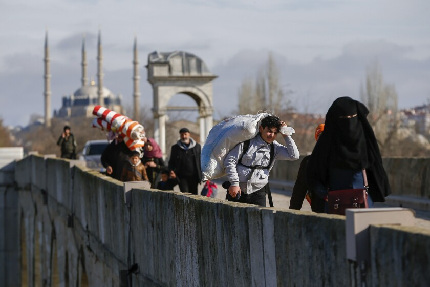 Migrants walk across a bridge near the Turkish-Greek border on Thursday.