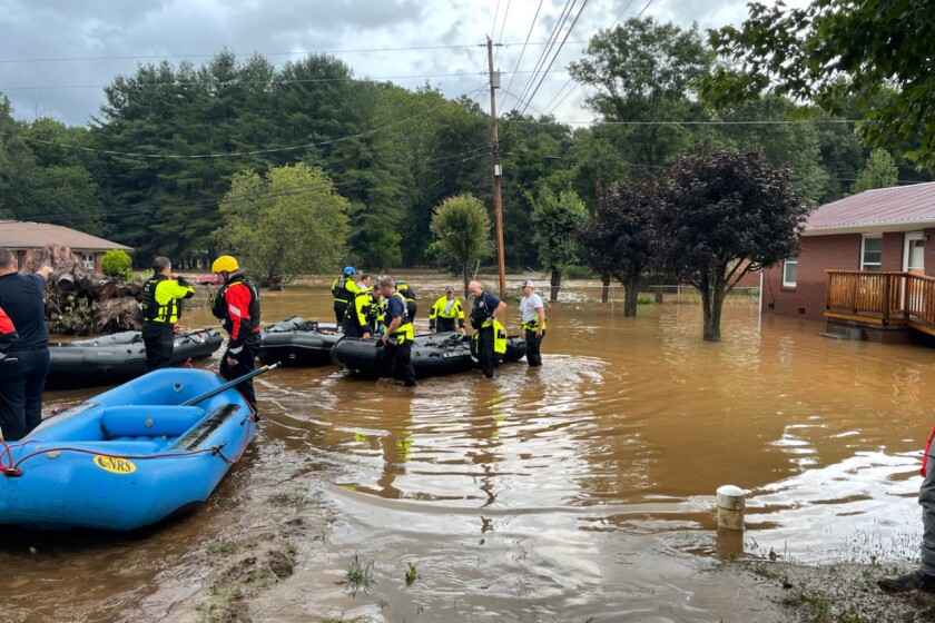 In this image provided by New Hanover County Fire Rescue, members of North Carolina's Task Force 11, based in New Hanover County, are shown during rescue efforts in Canton, N.C, on Tuesday, Aug. 17, 2021. Authorities said that dozens of water rescues were performed after the remnants of Tropical Storm Fred dumped rain on the mountains of North Carolina. (New Hanover County Fire Rescue via AP)