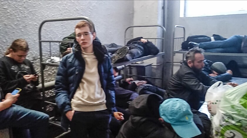 This image taken from a video filmed by Dmitry Shelomentsev shows, a group of detained people inside the deportation centre Sakharovo, 70km (43,7 miles) south-west of Moscow which was urgently transformed into a detention center in the absence of prison space, in Moscow, Russia, Thursday, Feb. 4, 2021. Dmitry Shelomentsev was among those who had to wait in a police bus for hours at Sakharavo before being taken in. Sentenced to 15 days in jail for participating in the Tuesday rally, Shelomentsev messaged the AP reporter on Feb. 4, 2021 morning from a cell for eight inmates where 28 people were held, awaiting transfer to smaller ones. (Dmitry Shelomentsev via AP)