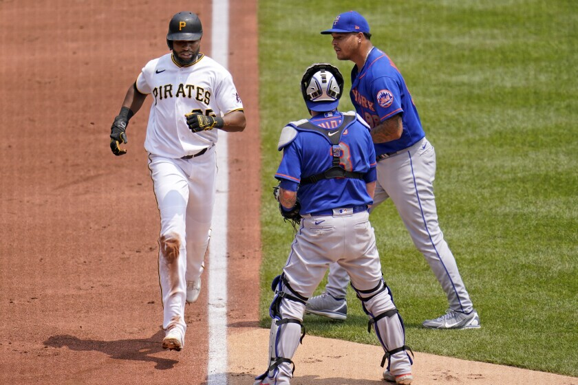 Pittsburgh Pirates' Gregory Polanco, left, scores past New York Mets starting pitcher Taijuan Walker, right, and catcher Tomas Nido on an infield hit by Kevin Newman and a fielding error during the first inning of a baseball game in Pittsburgh, Sunday, July 18, 2021. Three runs scored on the fielding error by Walker. (AP Photo/Gene J. Puskar)