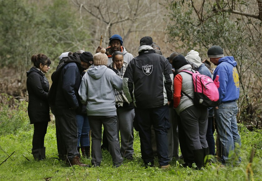 Family members and friends gather Monday near the banks of Alameda Creek where the vehicle of a missing 18-year-old woman was believed to be located.