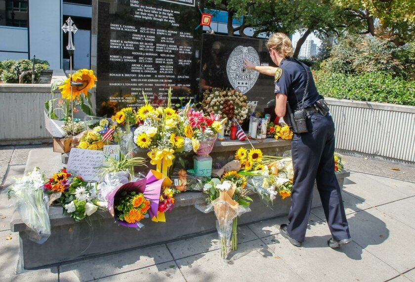 San Diego Community College Police officer Jane Obara touches the badge on the memorial to fallen officers at the San Diego Police Headquarters on Saturday in San Diego, California.