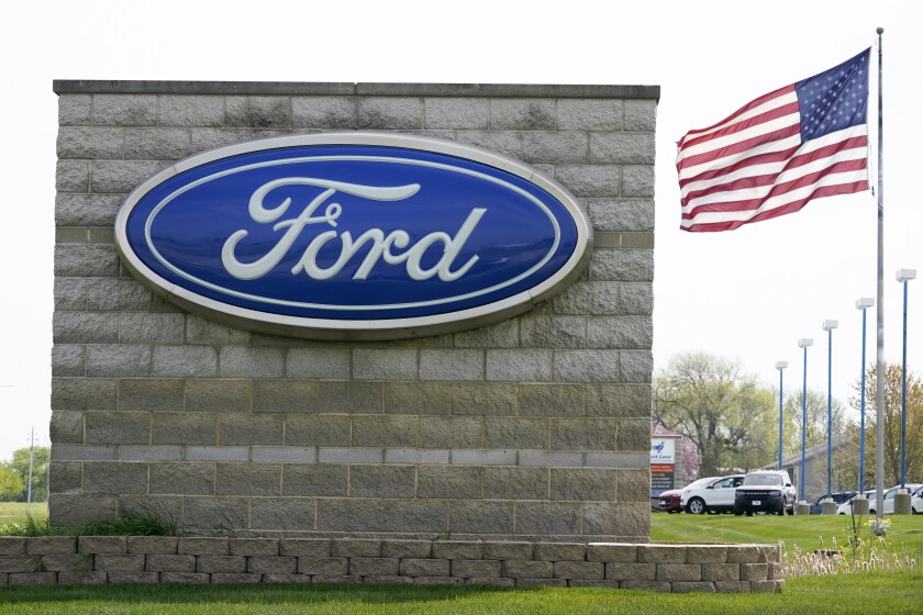 A United States flag flies over a Ford auto dealership, Tuesday, April 27, 2021, in Waukee, Iowa. Ford says it is starting to send out over-the-internet software updates to some of its newer models as it moves to offer technology to match electric car maker Tesla. At present the updates are only available on about 100,000 2021 model year F-150s, Mustang Mach-Es and the upcoming Bronco. (AP Photo/Charlie Neibergall)