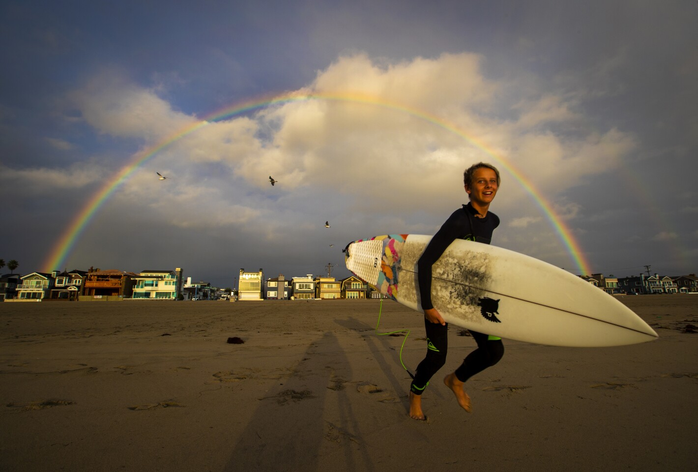 NEWPORT BEACH, CALIF. -- WEDNESDAY, MARCH 13, 2019: Surfer Jonah Haack, 13, of Newport Beach, revels in the appearance of a rainbow and excellent overhead surf conditions in between rain showers in Newport Beach, Calif., on March 13, 2019. (Allen J. Schaben / Los Angeles Times)
