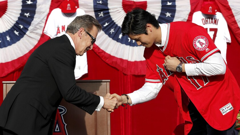 Angels owner Arte Moreno bows and congratulates Japanese superstar Shohei Ohtani after presenting him his No. 17 jersey during an introductory news conference on Saturday.
