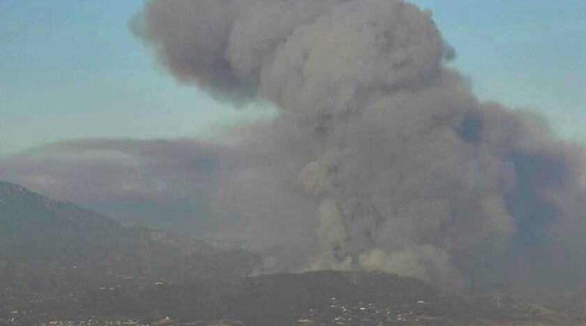 Black clouds of smoke emerge from the Apple fire near Cherry Valley in Riverside County.