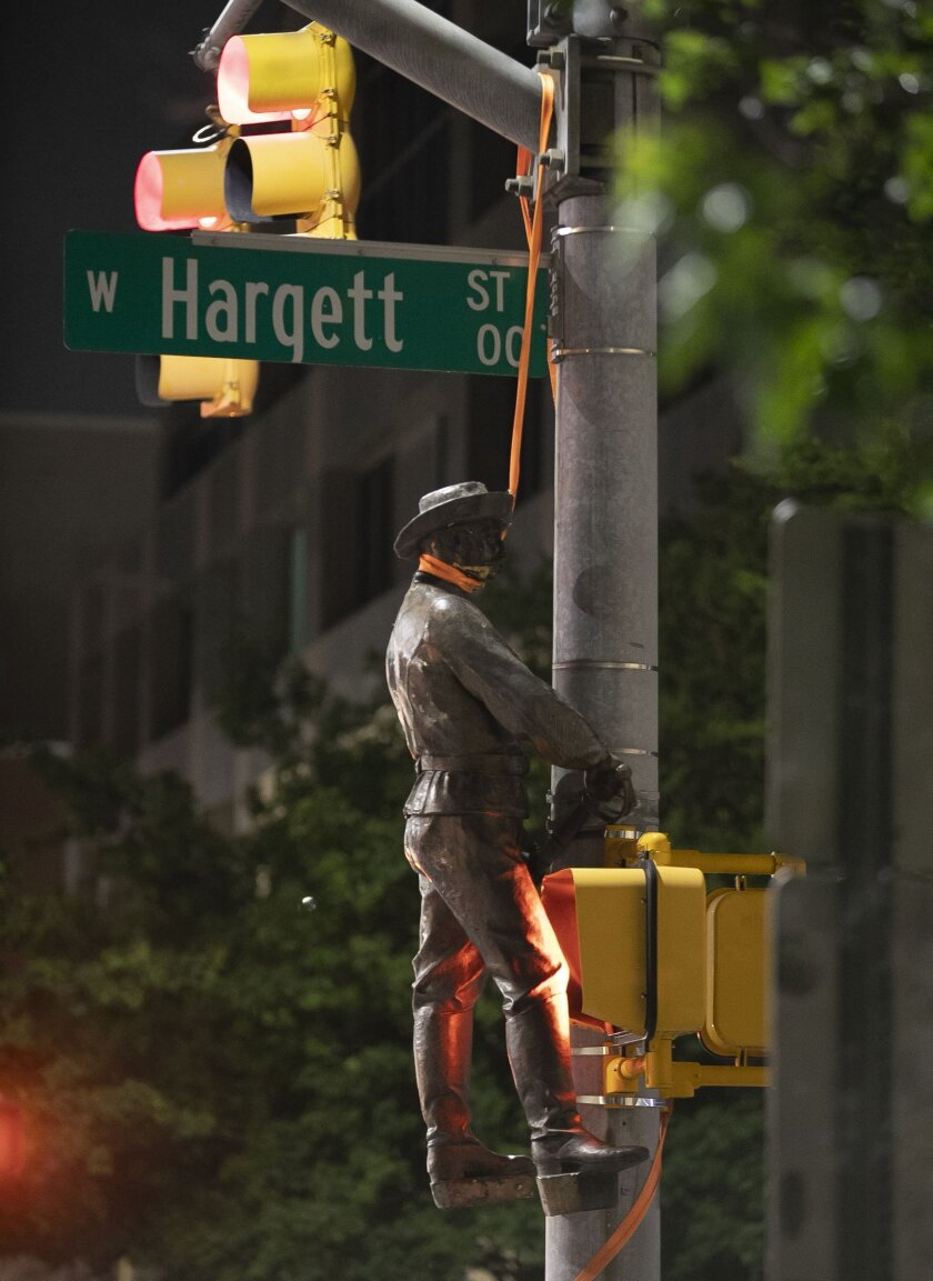 One of the Confederate statues that was felled from the Confederate monument on the west side of the North Carolina State Capitol by protesters is hung over a utility pole at the corner of Salisbury Street and Hargett Street, on Friday, June 19, 2020, in Raleigh, N.C. (Robert Willett/The News & Observer via AP)