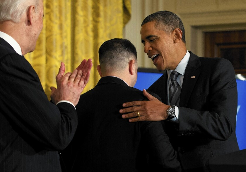 At the White House, President Obama talks with PG&E; apprentice electrician Erick Varela, center, a former U.S. Army combat infantryman in Iraq, as Vice President Joe Biden, left, applauds before Obama spoke about helping the long-term unemployed.