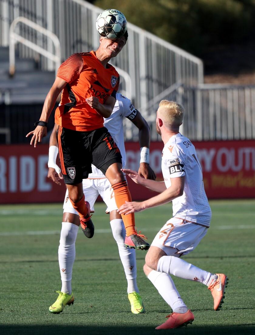 Orange County Soccer Club player Daniel Crisostomo, left, heads the ball in home match against the Phoenix Rising.