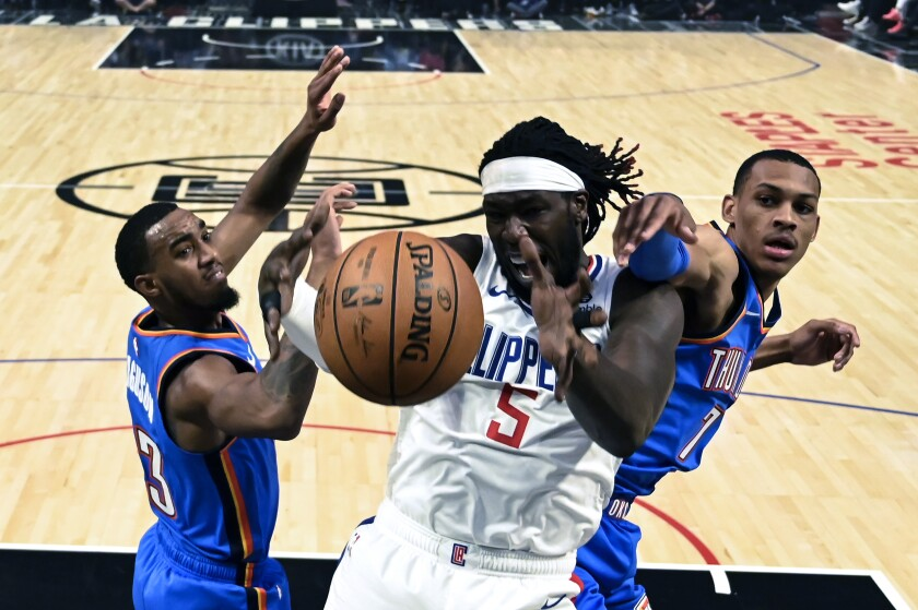 Clippers forward Montrezl Harrell (5) fights for a rebound with Thunder guard Terrance Ferguson (23) and forward Darius Bazley (7) during a game Nov. 18 at Staples Center.
