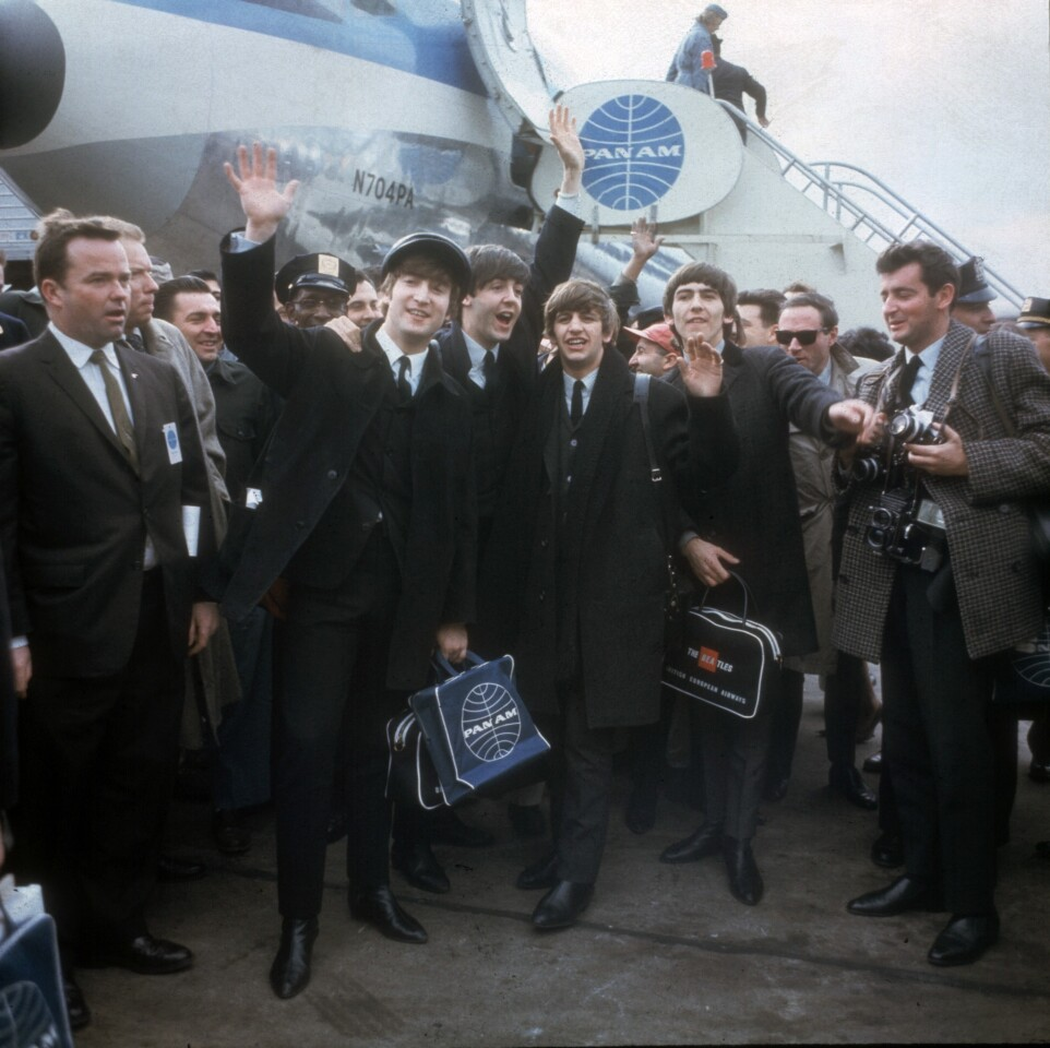 """The Beatles arrive at New York's Kennedy Airport on Feb. 7, 1964, for their first U.S. appearance. From left are John Lennon, Paul McCartney, Ringo Starr and George Harrison. Over the next two weeks, the Beatles stormed America, appearing on """"The Ed Sullivan Show"""" three times (the first two live and the third on tape) and playing concerts in front of thousands of fervid fans. By the time they flew home, the Fab Four was the most famous band in the world, and the nature of celebrity had changed forever."""