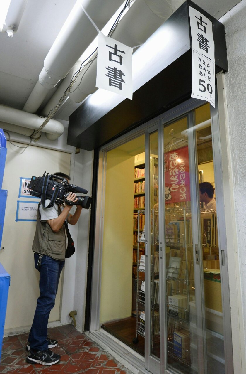 """A TV cameraman films a used-book store where a poster offering positions for """"work in Syria"""" was pasted on the wall in Tokyo Monday, Oct. 6, 2014. Japanese police questioned a university student and several others Monday over alleged plans to travel to Syria to join the Islamic State group, news reports said. Investigators believe that the student, who is on leave of absence from school, responded to the poster, Kyodo News said. The reported investigation by Tokyo police would be the first indication of support within Japan for the militant group. The letters on banners above reads: """"socondhand books."""" (AP Photo/Kyodo News) JAPAN OUT, MANDATORY CREDIT"""
