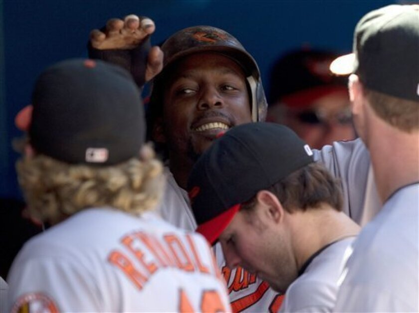 Baltimore Orioles' Vladimir Guerrero smiles as he is congratulated in the dugout after scoring during third inning baseball action against the Toronto Blue Jays in Toronto on Saturday, Sept. 10, 2011. (AP Photo/The Canadian Press, Frank Gunn)