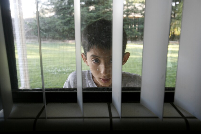 Joseph Gutierrez, 13, peeks into his kitchen window in Sanger, Calif. He has been diagnosed as mentally retarded, but his mother thinks he is autistic.