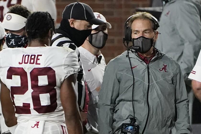 A masked Alabama coach Nick Saban speaks with defensive back Josh Jobe.