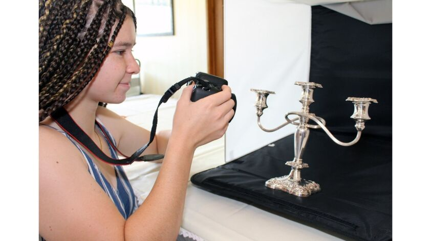 Glendale Community College student Isabelle Fishman takes digital shots of a silver candelabra, part