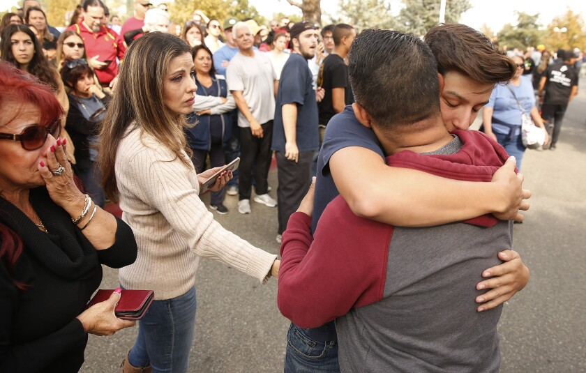 Saugus High School student hugs his parents
