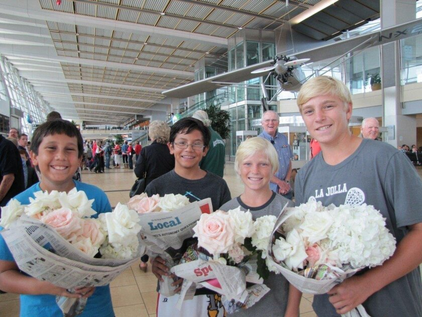 Operation Smile members Colin and Evan Steinwinder Landon and Morgan Watson bring flowers for the veterans coming home from a recent Honor Flight San Diego trip.