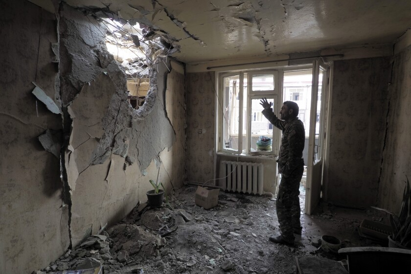 A man gestures in an apartment damaged by shelling by Azerbaijan's artillery in Stepanakert, Nagorno-Karabakh.