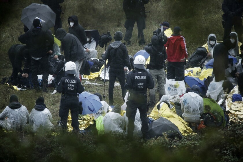Activists are surrounded by police on the Garzweiler power plant grounds in Grevenbroich, western Germany, Saturday, Sept. 26, 2020. Anti-coal protesters have entered a mine to protest the continued extraction and use of fossil fuels. (David Young/dpa via AP)
