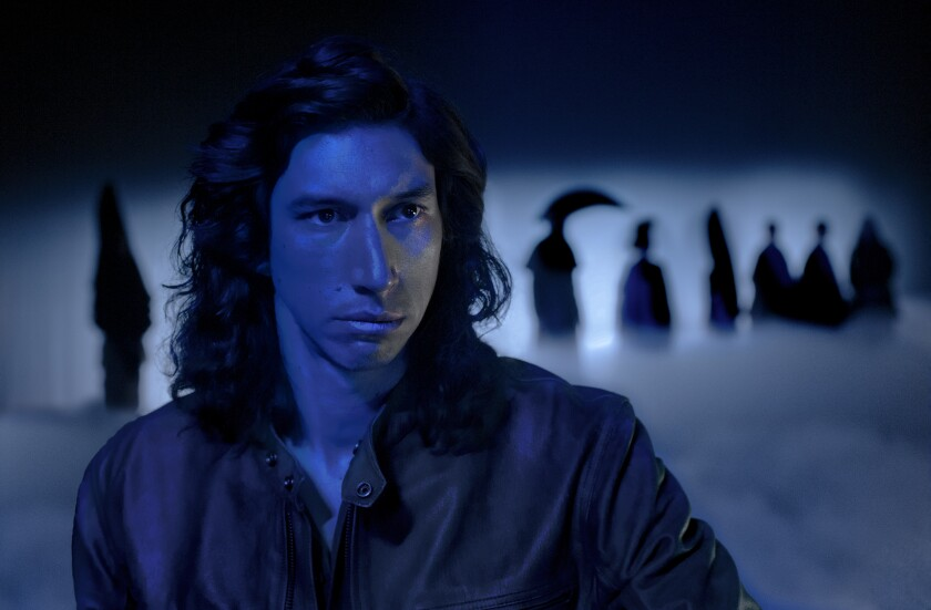A man with shoulder-length hair in dark lighting