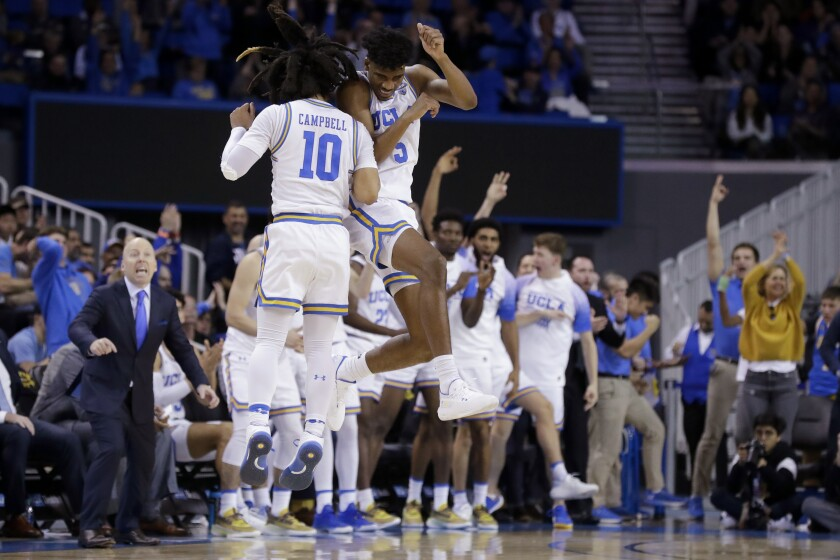 UCLA guard Chris Smith (5) celebrates with teammate Tyger Campbell after scoring during the second half of the Bruins' victory over Washington on Feb. 15, 2020, at Pauley Pavilion.