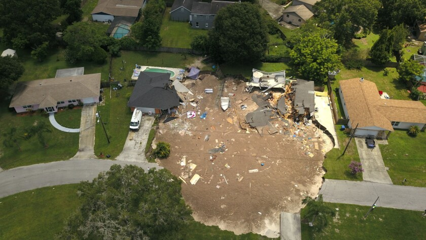 In this aerial photo, debris is strewn about after a sinkhole damaged two homes in Land O' Lakes, Fl