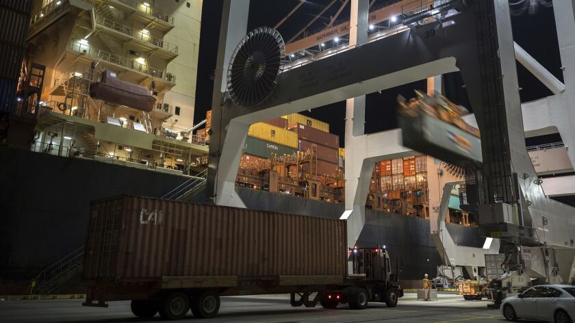 A crane loads a 40-foot shipping container onto a container ship at the Port of Savannah in Georgia.
