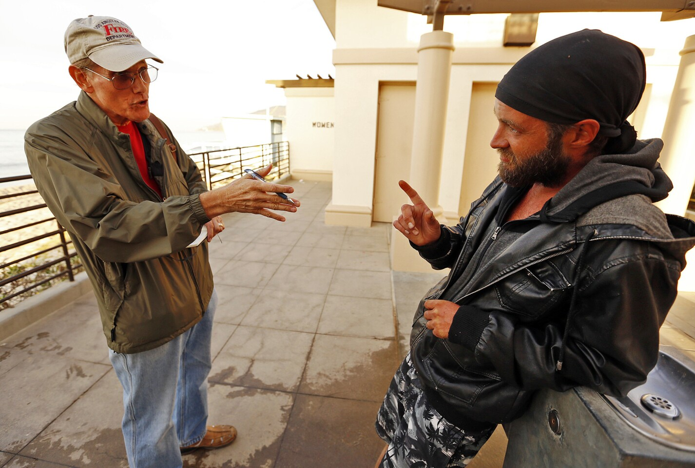 Patrick Hart, left, with the Pacific Palisades Task Force on Homelessness, talks to Brad Mark Kowalski, who is living near the beach, one of several homeless who are living in hidden encampments along Will Rogers State Beach.