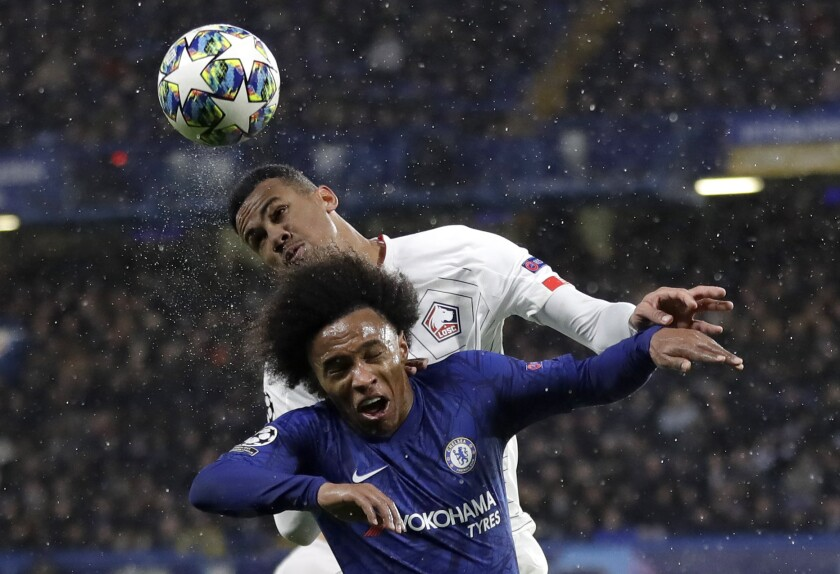 Chelsea's Willian fights for the ball against Lille's Gabriel, rear, during a Champions League soccer match.