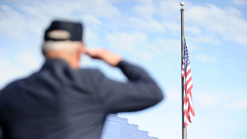 Veteran Al Santelli, of Mount Carmel, salutes the American flag as it is lowered to half-staff durin
