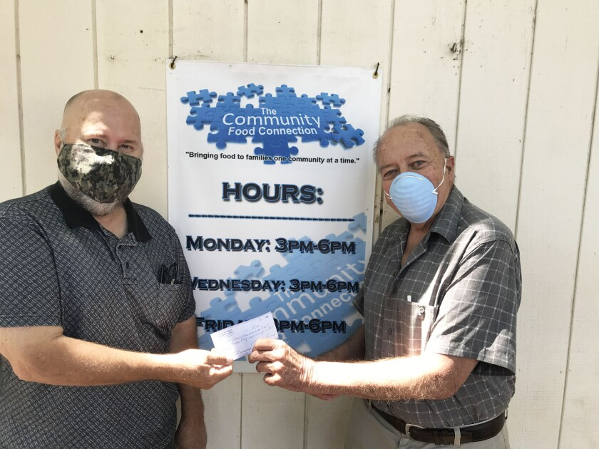 The Community Food Connection's Bill Rearick receiving the check from Patrick Korch.