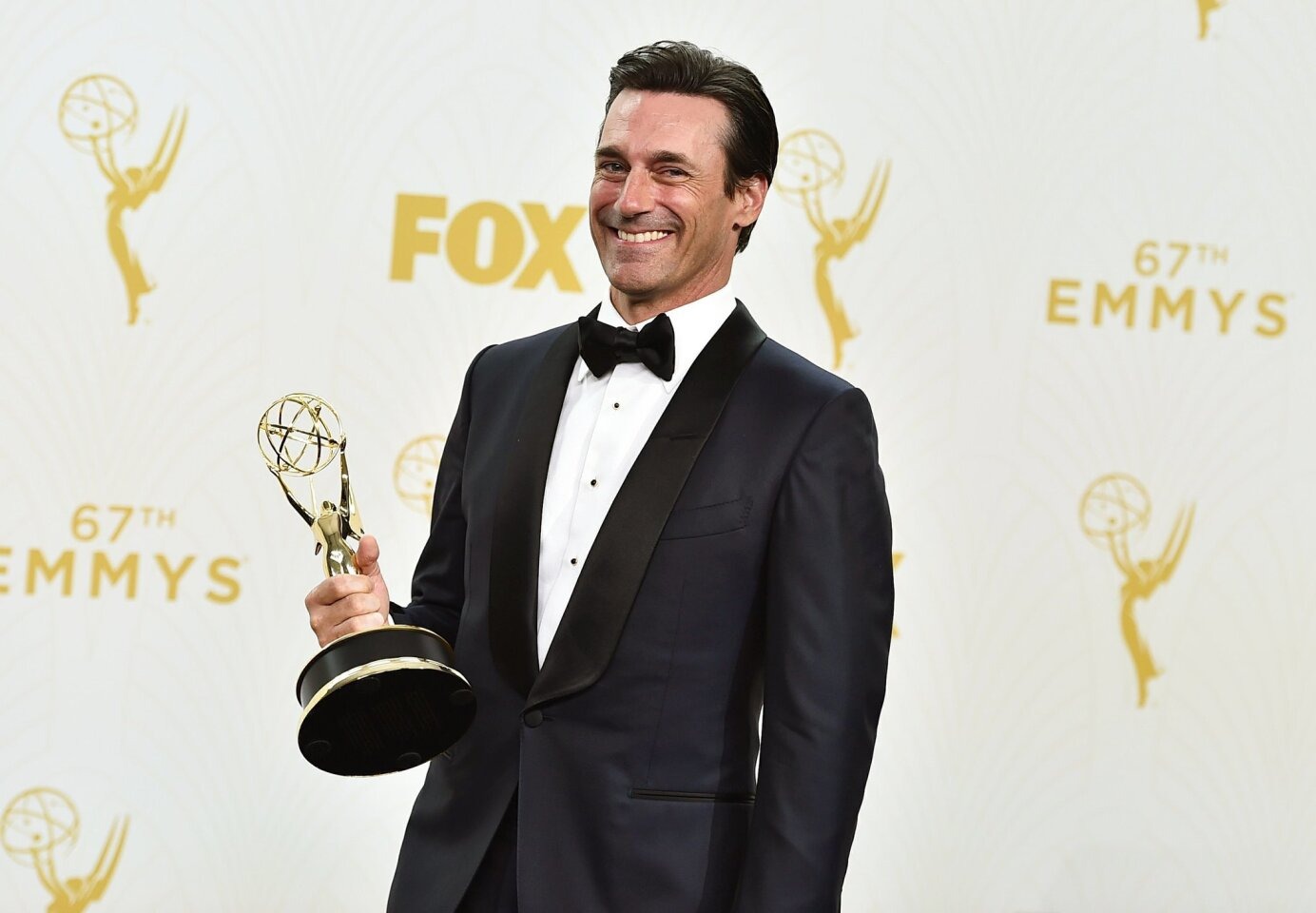 """Jon Hamm with the award for outstanding lead actor in a drama series for """"Mad Men"""" poses in the press room at the 67th Primetime Emmy Awards on Sunday, Sept. 20, 2015, at the Microsoft Theater in Los Angeles. (Photo by Jordan Strauss/Invision/AP)"""