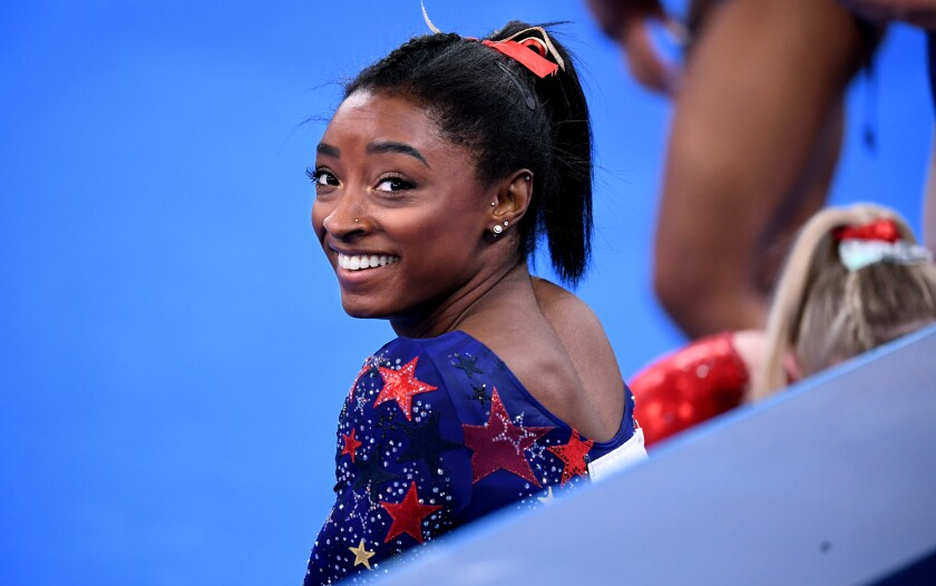 Simone Biles smiles in between sessions in the women's team qualifying at the 2020 Tokyo Olympics.
