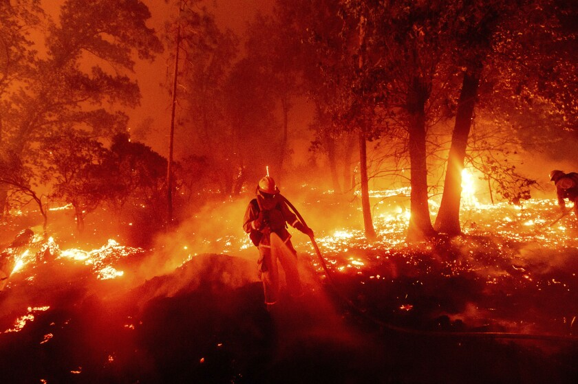 FILE - In this Sept. 7, 2020, file photo, a firefighter battles the Creek Fire as it threatens homes in the Cascadel Woods neighborhood of Madera County, Calif. Climate-connected disasters seem everywhere in the crazy year 2020. But scientists Wednesday, Sept. 9, say it'll get worse. (AP Photo/Noah Berger, File)