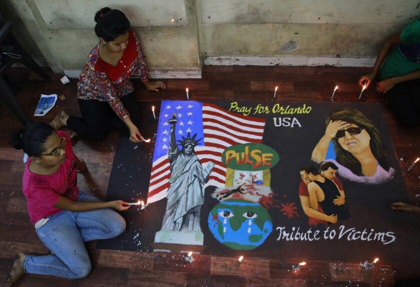 Estudiantes de arte en Mumbai, India, encienden velas frente a un mural en recuerdo de las víctimas de una balacera en Orlando, Florida, el lunes 13 de junio de 2016. Una balacera el fin de semana dejó al menos 50 personas en un club nocturno gay en Florida. (AP Foto/Rafiq Maqbool)